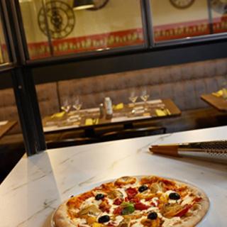 Cette image présente une pizza dans le restaurant Pizzeria